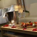 Tisch im Zimmer mit romantischer Dekoration Sekt und Pralinen