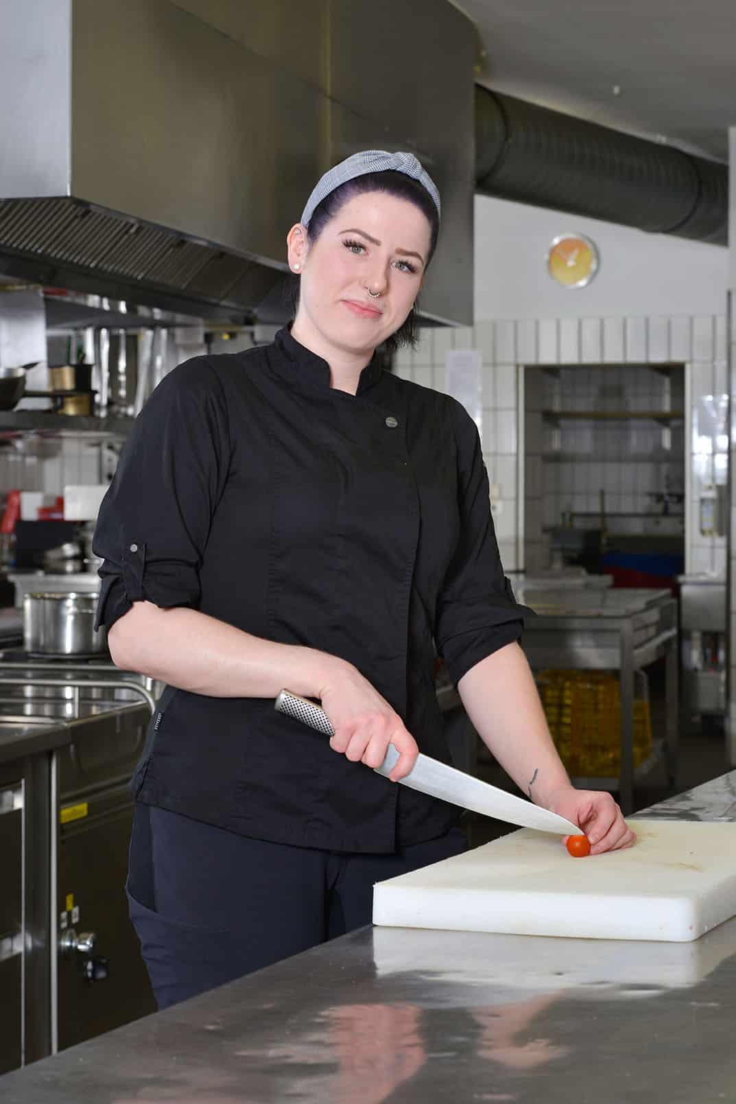 Köchin in der Küche am Schneidebrett