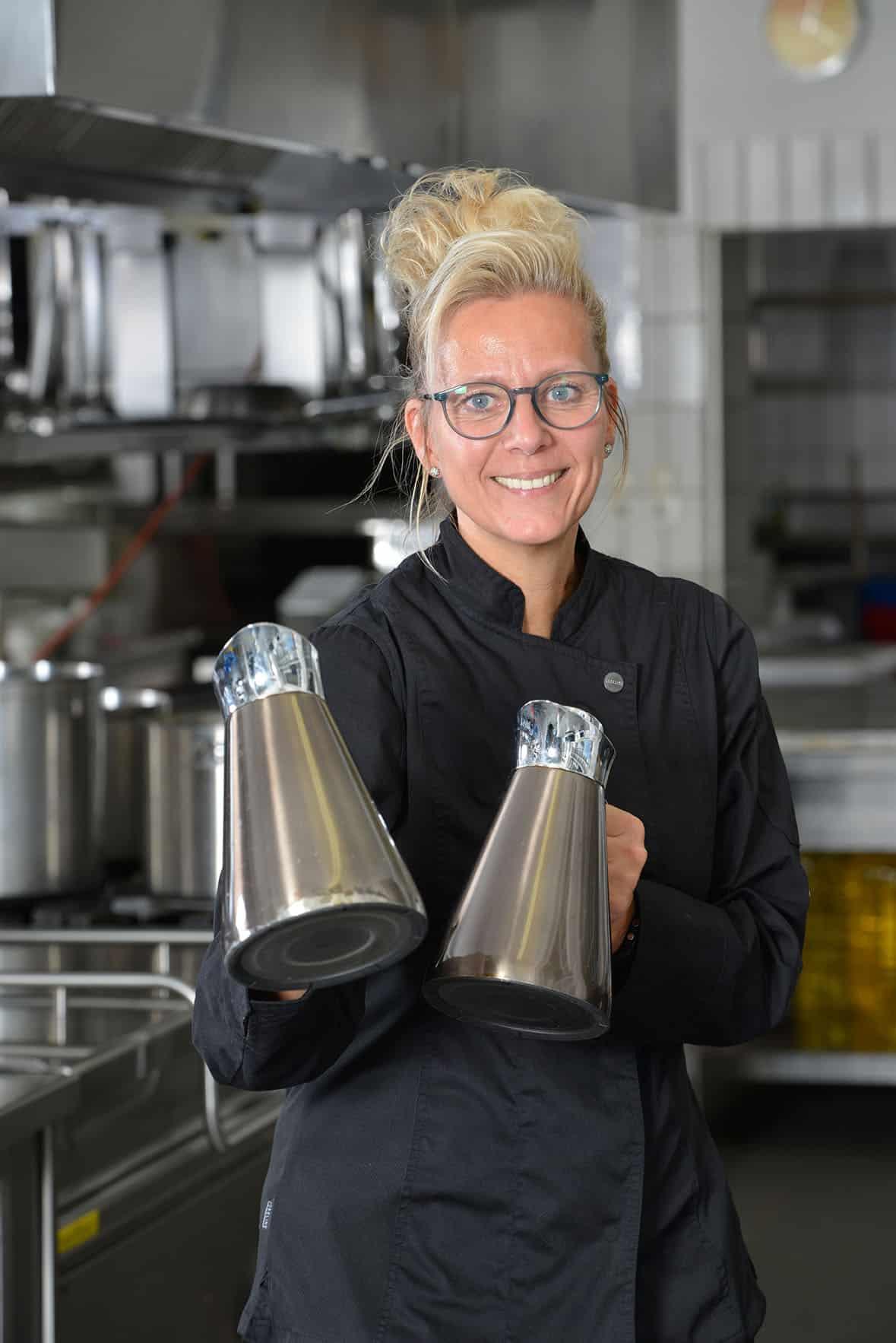 Köchin mit 2 Kaffeekannen in der Hand