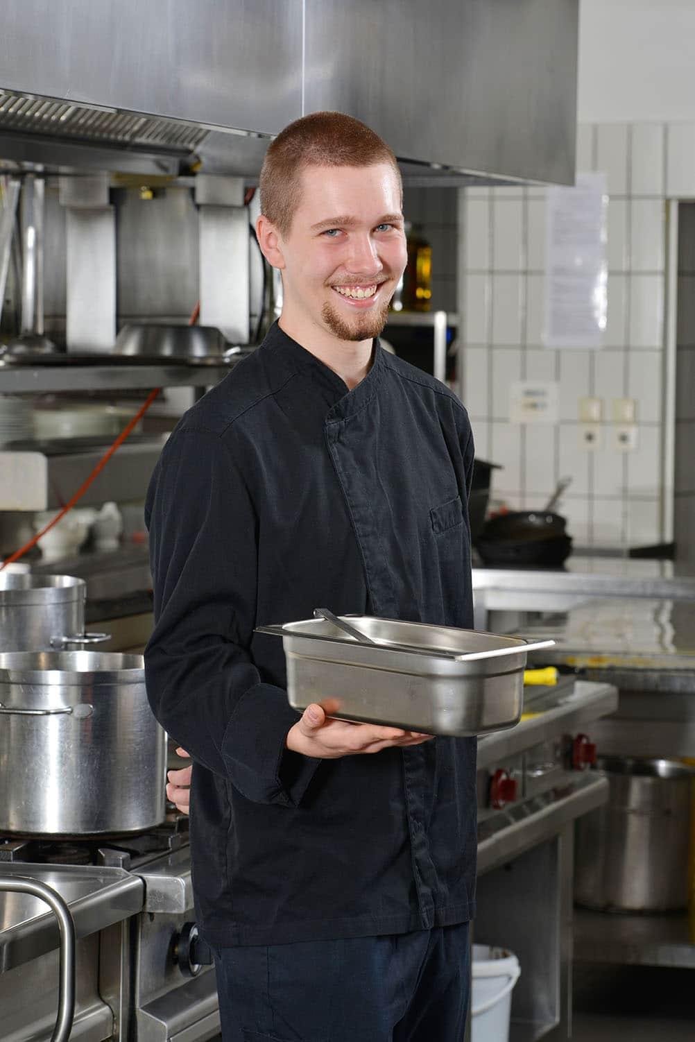 Koch mit Schüssel in der Hand in der Küche