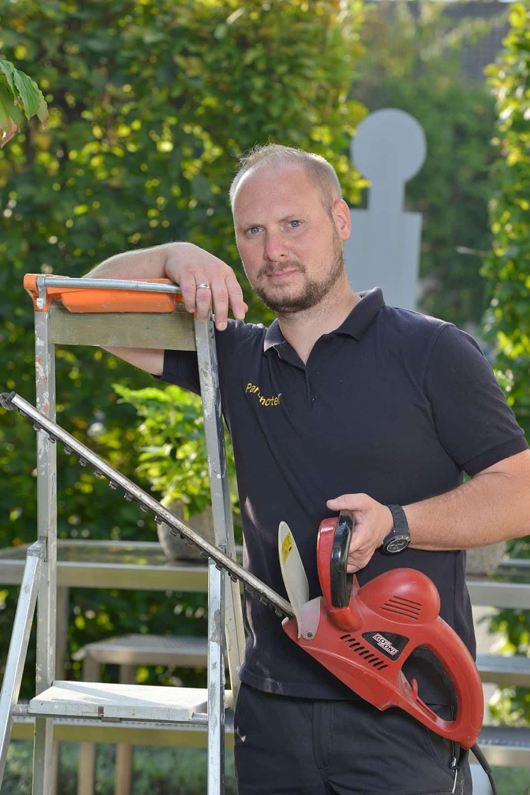 Handwerker mit Leiter und Heckenschere