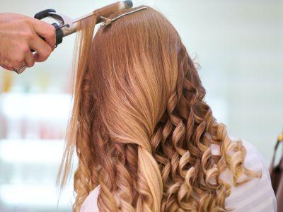 Schmuckbild Frau von hinten mit blonden Haaren und Lockenstab