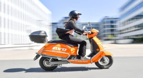 E-Roller orange EVO mit Fahrer fahrend